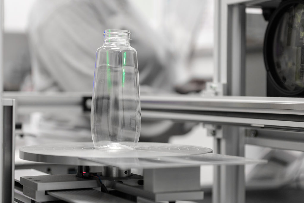 Photo of clear bottle on quality assurance machine